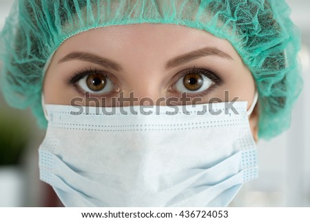 Close-up portrait of young female surgeon doctor or intern wearing protective mask and hat. Healthcare, medical education, emergency medical service, surgery or veterinary concept - stock photo