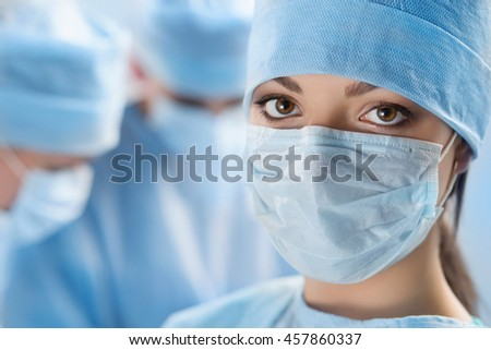 Close up portrait of young female surgeon doctor surrounded by her team. Group of surgeon in operation theatre. Healthcare, medical education, emergency medical service and surgery concept - stock photo