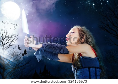 Close up portrait of young female vampire holding big knife. Castle towers and crows flaying in full moon background. - stock photo
