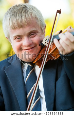 Close up portrait of young handicapped violinist outdoors. - stock photo