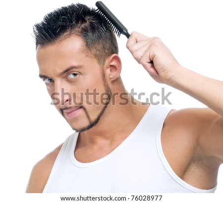 Close up portrait of young handsome man with perfect skin and hair using comb brush. Isolated on white - stock photo