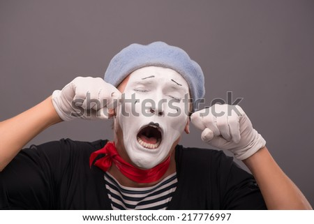 Close-up Portrait of young male mime with white face, grey hat crying, shouting and wiping his tears isolated on grey background with copy place - stock photo