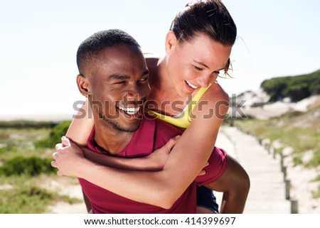 Close up portrait of young man carrying his girlfriend on his back - stock photo