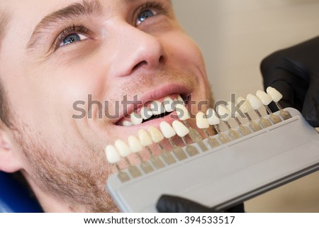 Close up portrait of Young man in dentist chair, Check and select the color of the teeth. Dentist makes the process of treatment in dental clinic office.Dentist - stock photo
