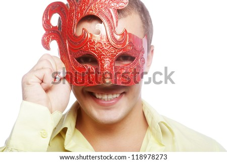 Close up portrait of young man with carnival mask against white background. - stock photo