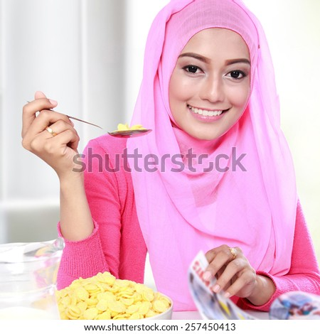 close up portrait of young muslim woman eating a cereal while reading a magazine - stock photo