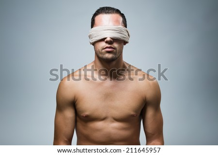 Close-up portrait of young naked blindfold man. - stock photo