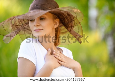 Close-up portrait of young nice smiling woman wearing brown fashionable hat at summer green park. - stock photo