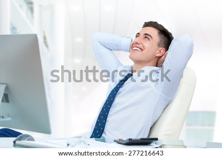 Close up portrait of young office worker relaxing in office. Young man sitting at desk with hands behind head and looking up. - stock photo