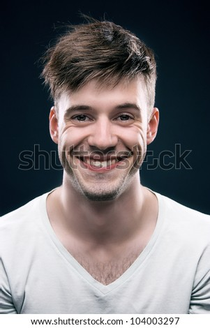 Close up portrait of young positive smiling man on a gray background - stock photo