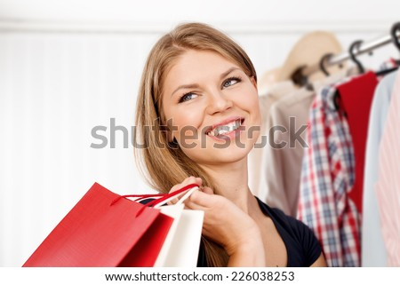 Close up portrait of young pretty woman buyer with purchases in shopping mall. Happy female customer standing with shopping bags at clothes rack.  - stock photo