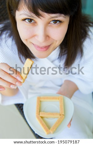 Close-up Portrait of young pretty woman with rage eats wafer - stock photo