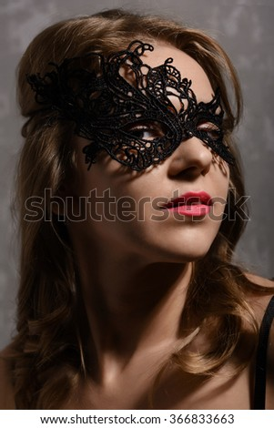 Close-up portrait of young sensual ginger woman wearing black party mask - stock photo
