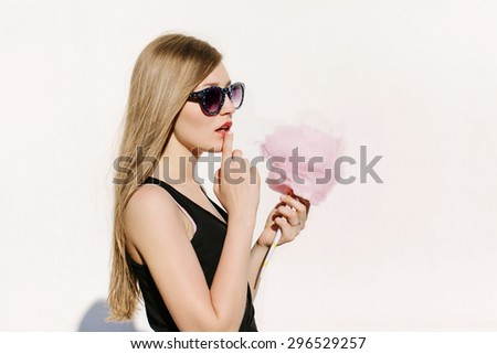 Close up portrait of young sexy surprised woman with pink cotton candy. Lifestyle portrait. White background, not isolated - stock photo