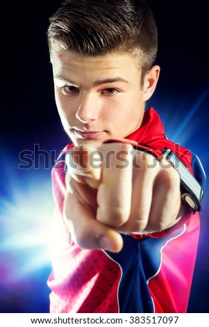 Close up portrait of young sports man pointing with finger at camera. Handsome teen boy isolated against abstract dark background. - stock photo