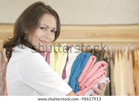 Close up portrait of young store attendant holding a pile of clothes in a fashion store. - stock photo