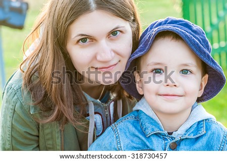 close up portrait of young woman and her boy child - family of mother and son - stock photo