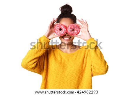 Close up portrait of young woman covering her eyes with donuts on white background - stock photo