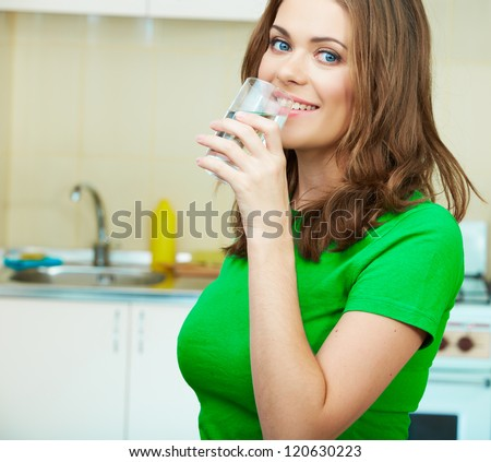 Close up portrait of Young Woman drinking water at home interior. Clothes of green color. - stock photo