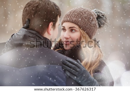 Close-up portrait of young woman, embracing boyfriend. Winter season. - stock photo