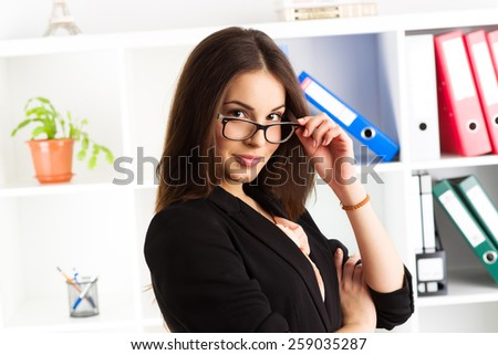 Close-up portrait of young woman entrepreneur standing in her office. Concept of leadership and confidence in business. - stock photo