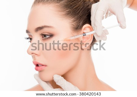 Close up portrait of young  woman getting cosmetic injection with  syringe - stock photo