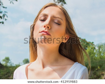 Close up portrait of young woman in white dress outdoor in nature, eyes closed, meditating, trees and sky in background  - stock photo