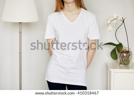 Close up portrait of young woman posing against home interior background with a floor lamp and flowers. Cropped view of pretty Caucasian teenage redhead girl in blank white T-shirt for your content. - stock photo