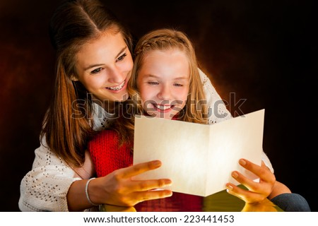 Close up portrait of young Woman reading Christmas card to youngster. - stock photo