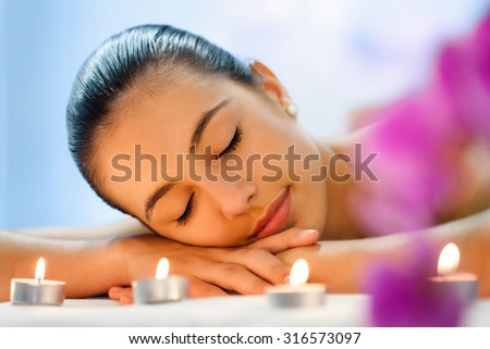 Close up portrait of Young woman relaxing in dimmed candle light after massage. - stock photo
