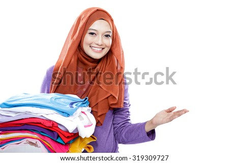 close up portrait of young woman wearing hijab carrying folded clean clothes while presenting copy space isolated on white - stock photo