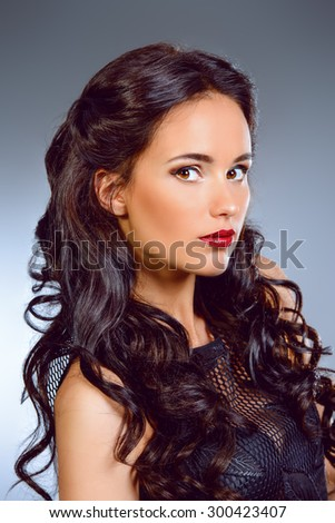 Close-up portrait of young woman with beautiful brunette hair. Make-up, cosmetics. - stock photo