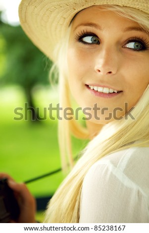 Close-up portrait of young woman with camera - stock photo