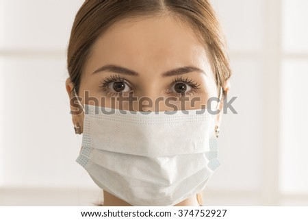 Close up portrait of young woman with medicine health care mask against white room background - stock photo
