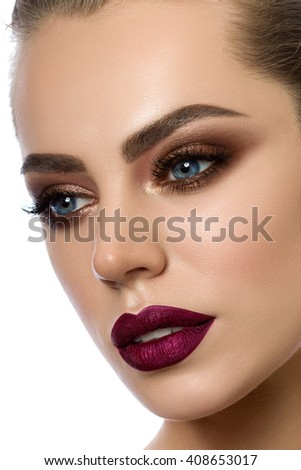 Close-up portrait of young woman with wine red lips and bronze smokey eyes. Modern fashion make-up. Studio shot - stock photo