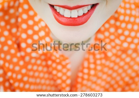 close-up portrait outdoors young beautiful girl in an orange hipster blonde bright cheerful polka dot blouse , smiling red plump lips on the background of green grass  with white teeth - stock photo
