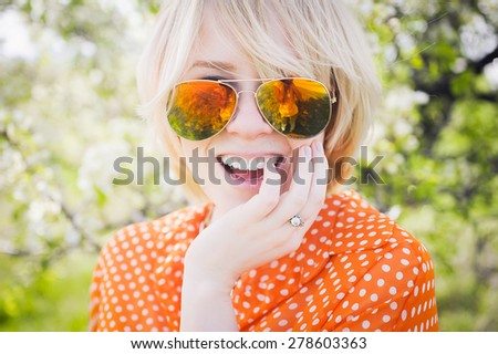 close-up portrait outdoors young beautiful girl in an orange hipster blonde bright cheerful polka dot blouse and smiling in SLR sunglasses on a background  blooming trees  with white teeth - stock photo