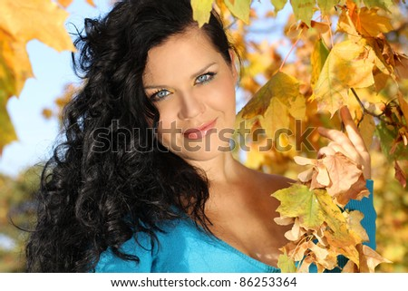 Close up Portrait smiling woman in autumn leaves outdoors - stock photo