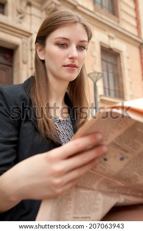 Close up portrait view of an attractive professional young woman sitting by a classic stone building in the city reading a financial newspaper, outdoors. Business communications and information. - stock photo
