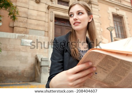 Close up portrait view of an attractive professional young woman sitting by a classic stone building in the city reading a financial newspaper, thoughtful outdoors. Business communications and news. - stock photo