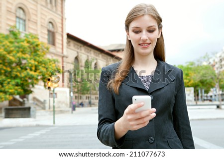 Close up portrait view of an attractive smiling young professional businesswoman using smartphone technology in a classic city, outdoors. (Business, People, Technology) - stock photo