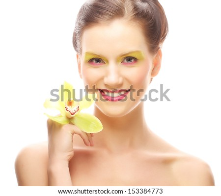 Close up portrait young woman with bright make up holding orchid - stock photo