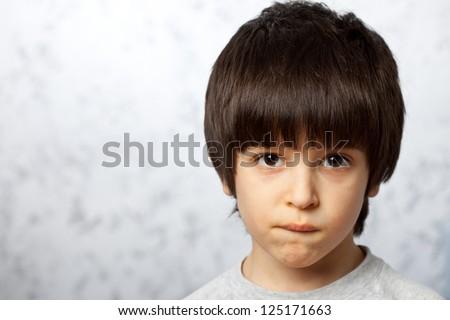 close-up portraits of thoughtful boy bit his li - stock photo