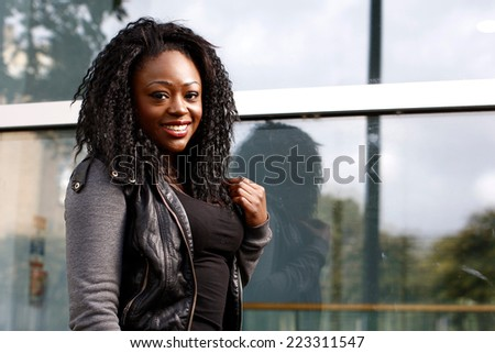 Close up Positive Attitude Black Woman in Jacket Looking at Camera. isolated on Building Glass Wall. - stock photo