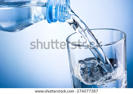 Close-up pouring water from bottle into glass on a blue background - stock photo