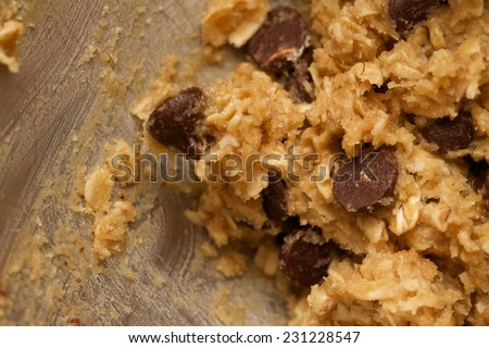 Close up preparation of an abstract texture background for homemade chocolate chip oatmeal cookie dough batter inside a baking mixer. These cookies are sweet desserts for snacks  - stock photo