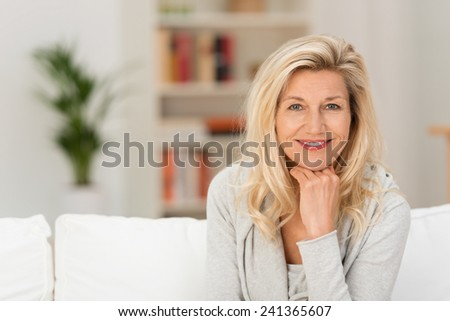 Close up Pretty Adult Woman Sitting on White Sofa with Hand on the Chin. Captured her While Looking at the Camera. - stock photo
