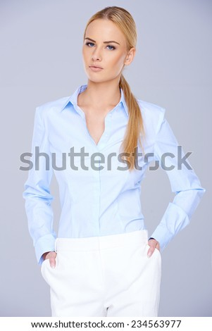 Close up Pretty Blond Woman in Light Blue Long Sleeve Blouse and White Pants. Looking at the Camera on Gray Background. - stock photo