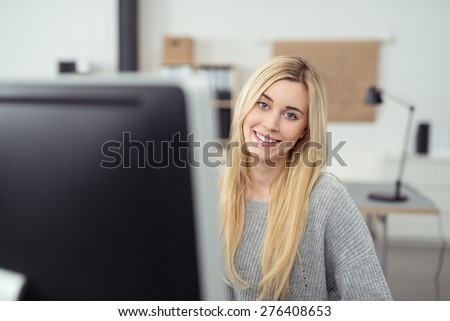 Close up Pretty Blond Woman Sitting at her Desk with Computer Monitor Inside the Office, Looking at Camera. - stock photo