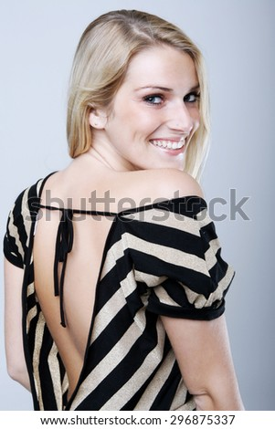 Close up Pretty Blond Woman Wearing Backless Striped Shirt, Smiling at the Camera, Isolated on Gray Background. - stock photo